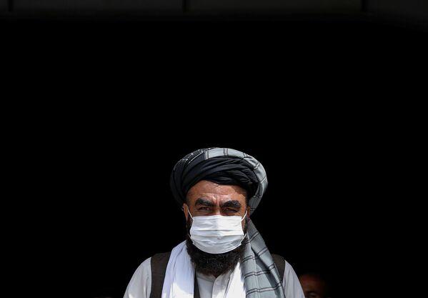 Мужчина в медицинской маске во время бесплатной раздачи продовольствия нуждающимся в Кабуле - Sputnik Таджикистан
