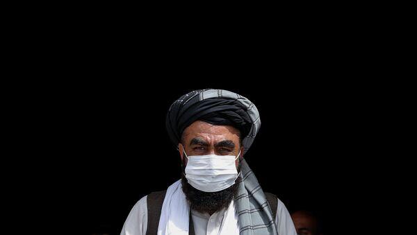 Мужчина в медицинской маске во время бесплатной раздачи продовольствия нуждающимся в Кабуле - Sputnik Тоҷикистон