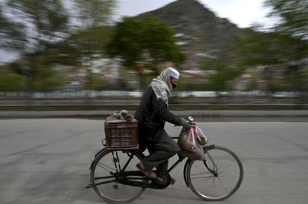 Мужчина в защитной маске едет на велосипеде по Кабулу, Афганистан - Sputnik Таджикистан