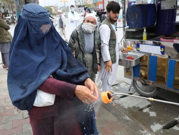 Сотрудники афганской национальной службы закупок распыляют дезинфицирующее средство на руки женщины - Sputnik Таджикистан