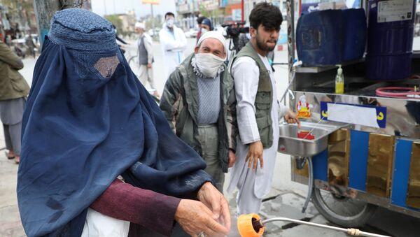 Сотрудники афганской национальной службы закупок распыляют дезинфицирующее средство на руки женщины - Sputnik Тоҷикистон