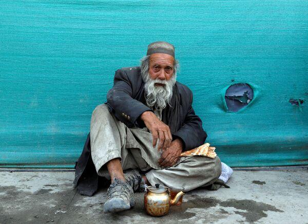 Бездомный мужчина пьет чай в придорожном чайном магазине в Кабуле, Афганистан - Sputnik Таджикистан
