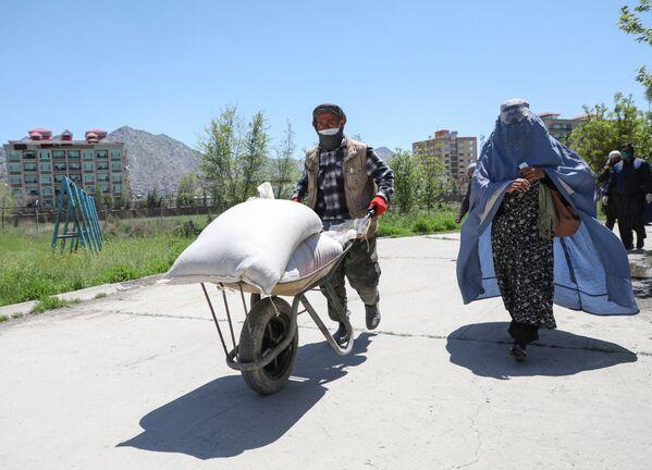 Афганец везет на телеге один из мешков с пшеницей, пожертвованных правительством Афганистана в качестве помощи населению, Кабул - Sputnik Таджикистан