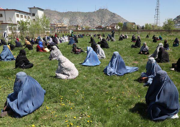 Женщины ждут бесплатное продовольствие на газоне в Кабуле, Афганистан  - Sputnik Таджикистан