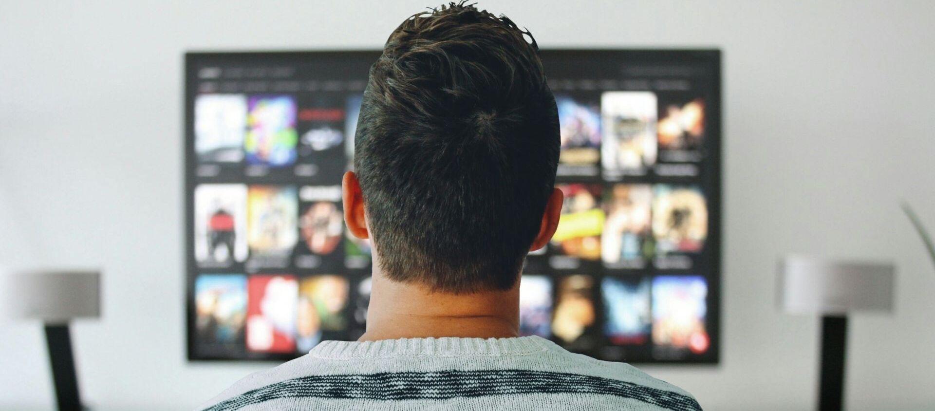 Мужчина смотрит телевизор - Sputnik Таджикистан, 1920, 10.02.2021