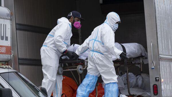 Медицинские сотрудники перевозят тела в рефрижераторный грузовик - Sputnik Таджикистан