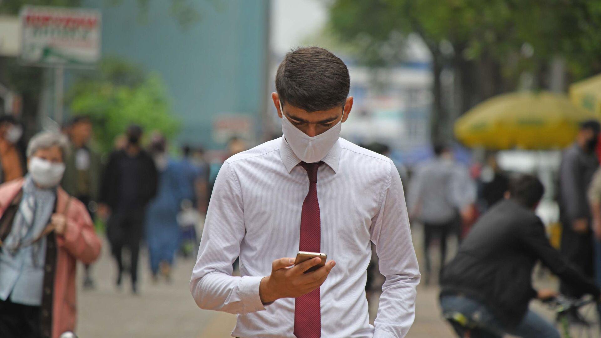 Мужчина в маске смотрит на телефон - Sputnik Таджикистан, 1920, 22.08.2021