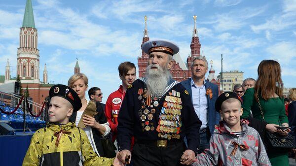 Ветеран с детьми перед началом военного парада в ознаменование 70-летия Победы в Великой Отечественной войне 1941-1945 годов - Sputnik Тоҷикистон