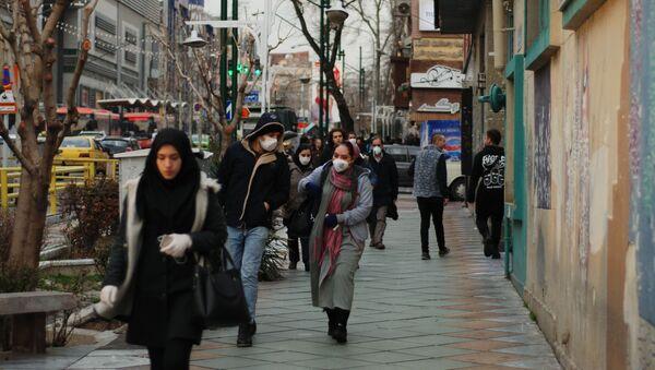 Жители Тегерана идут по одной из центральных улиц в медицинских масках.  - Sputnik Тоҷикистон