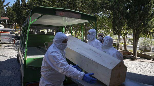 Работники морга погружают гроб с погибшим от коронавируса, архивное фото - Sputnik Таджикистан