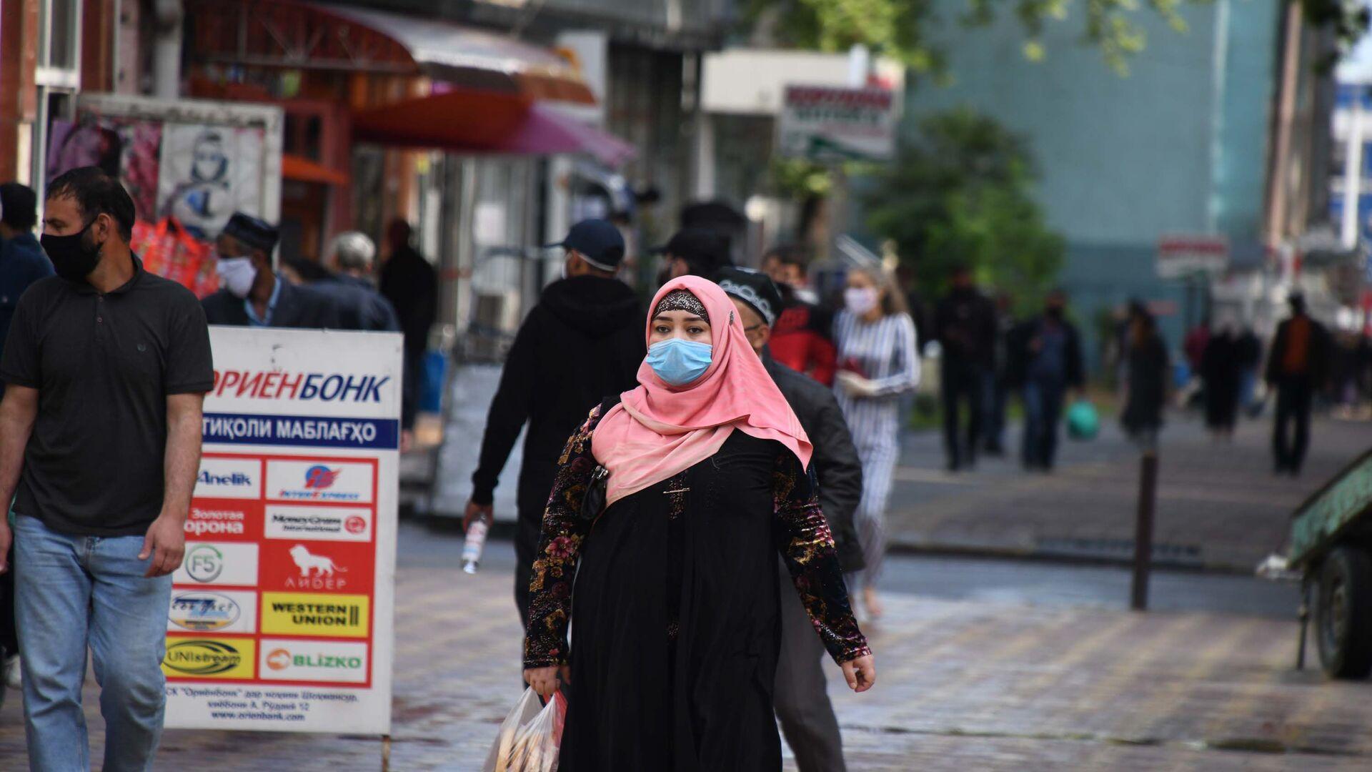 Женщина в защитной маске на улице города Душанбе - Sputnik Тоҷикистон, 1920, 03.09.2021