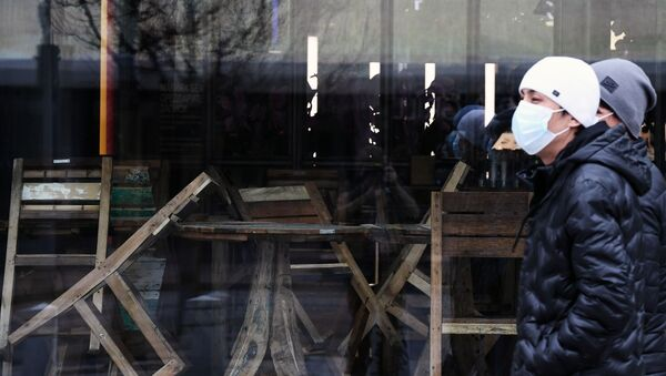 Люди в медицинских масках идут мимо закрытого кафе, архивное фото - Sputnik Таджикистан
