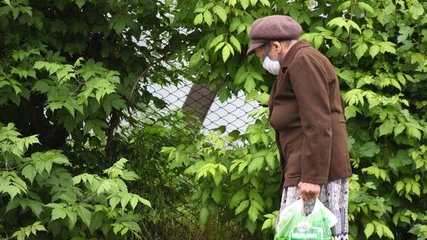 Пожилая женщина в защитной маске - Sputnik Тоҷикистон