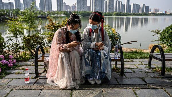 Молодые женщины в масках и в традиционных костюмах на скамейке в парке Уханя, Китай - Sputnik Тоҷикистон