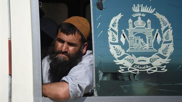 Талиб выглядывает из автобуса после освобождения из тюрьмы Баграм, Афганистан - Sputnik Таджикистан