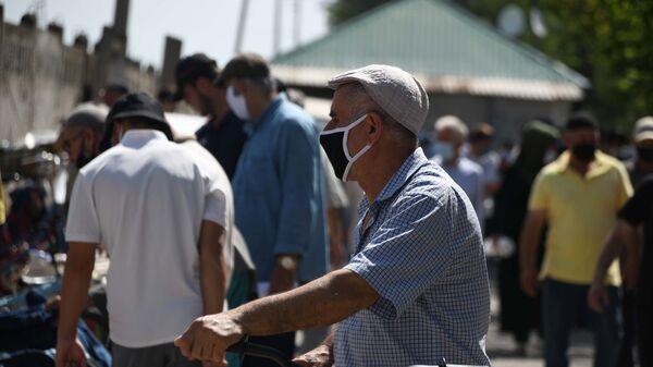 Человек в защитной маске в городе Душанбе - Sputnik Тоҷикистон