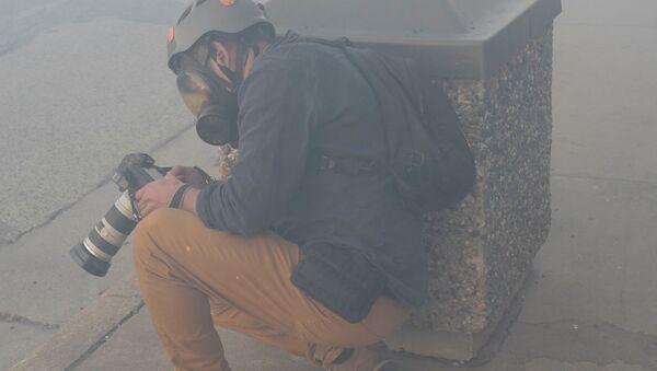 Фотокорреспондент Reuters Карлос Барриа прячется за мусорным баком от государственного патруля штата Миннесота - Sputnik Тоҷикистон