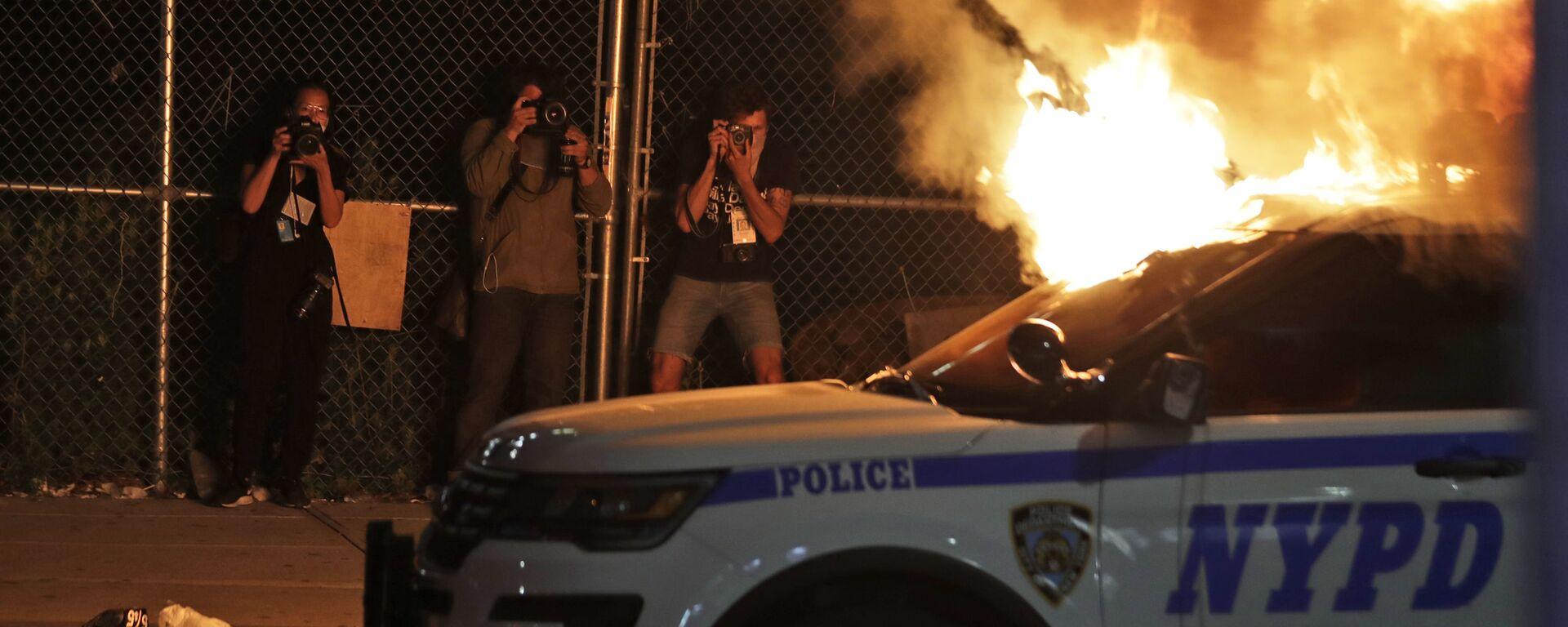 Фотографы во время съемки горящей полицейской машины в Нью-Йорке  - Sputnik Таджикистан, 1920, 24.04.2021
