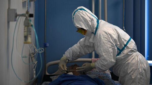 Врач и пациент в госпитале для лечения больных COVID-19 - Sputnik Тоҷикистон