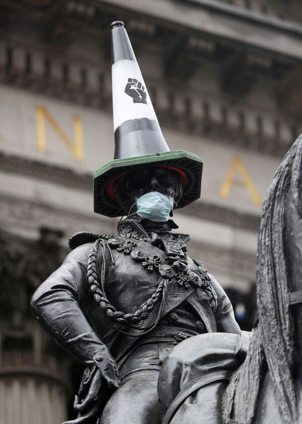 Конная статуя герцога Веллингтона с дорожным конусом на голове и с маске после акций протеста в Глазго, Великобритания - Sputnik Таджикистан