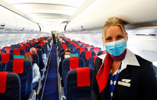 Стюардесса в медицинской маске в салоне самолета в международном аэропорту Брюсселя - Sputnik Таджикистан