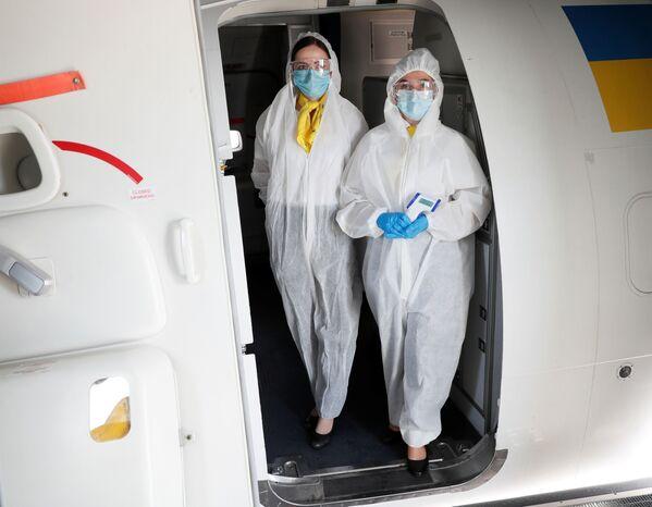 Стюардессы в защитных костюмах на входе в самолет в международном аэропорту Борисполь в Киеве - Sputnik Таджикистан