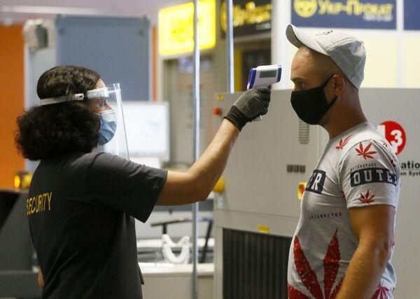 Пассажир в защитной маске проходит температурный контроль в международном аэропорту Борисполь в Киеве - Sputnik Таджикистан