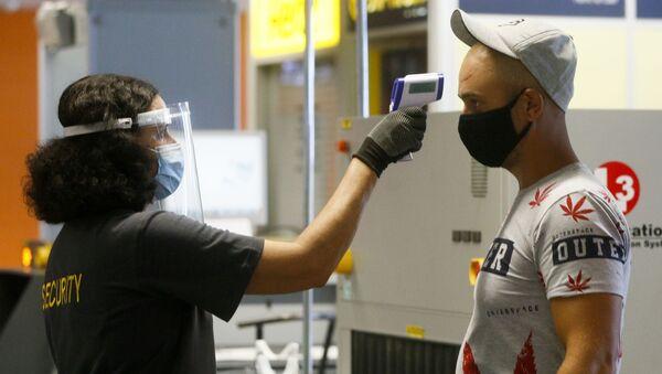 Пассажир в защитной маске проходит температурный контроль в международном аэропорту Борисполь в Киеве - Sputnik Тоҷикистон