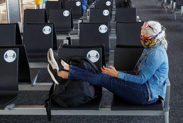 Пассажирка в защитной маске в терминале  международного аэропорта Брюсселя - Sputnik Таджикистан