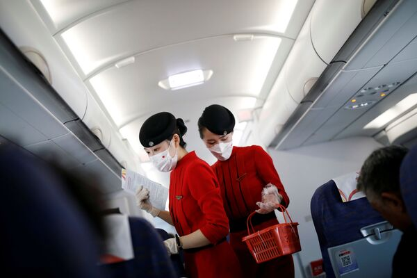 Бортпроводницы в масках и перчатках на борту самолета авиакомпании Сычуань, Китай - Sputnik Таджикистан
