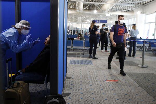 Прибывшего из Катара пассажира тестируют на коронавирус в международном аэропорту Элефтериос Венизелос в Афинах - Sputnik Таджикистан