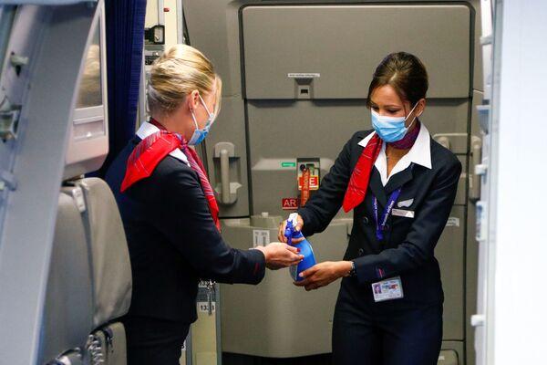 Стюардессы в медицинских масках обрабатывают руки антисептическим гелем в салоне самолета в международном аэропорту Брюсселя - Sputnik Таджикистан