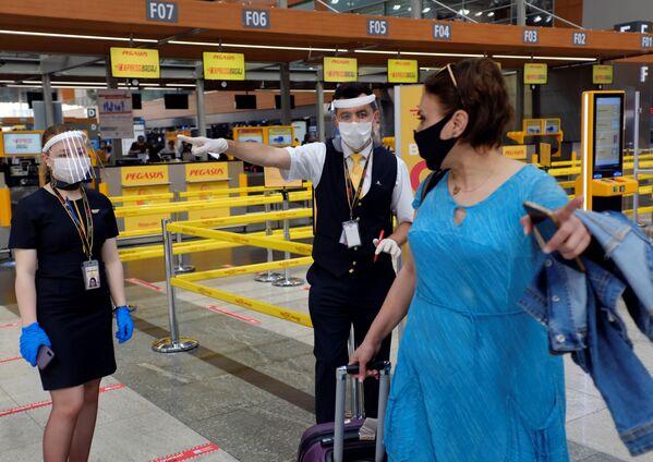 Сотрудники авиакомпании Pegasus Airlines в защитных масках и экранах указывают пассажиру нужное направление в международном аэропорту имени Сабихи Гекчен в Стамбуле - Sputnik Таджикистан