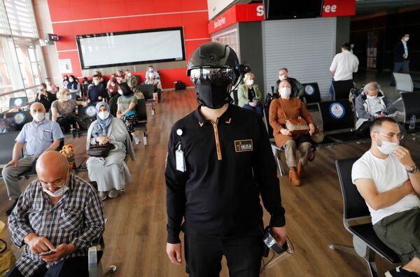 Сотрудник службы безопасности в тепловизионном шлеме следит за пассажирами, ожидающими посадки на рейс в аэропорту Стамбула - Sputnik Таджикистан