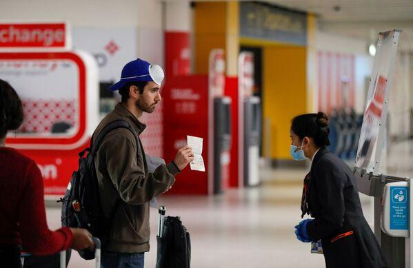 Пассажир предъявляет свой паспорт сотруднику в аэропорту Гатвик, Великобритания - Sputnik Таджикистан