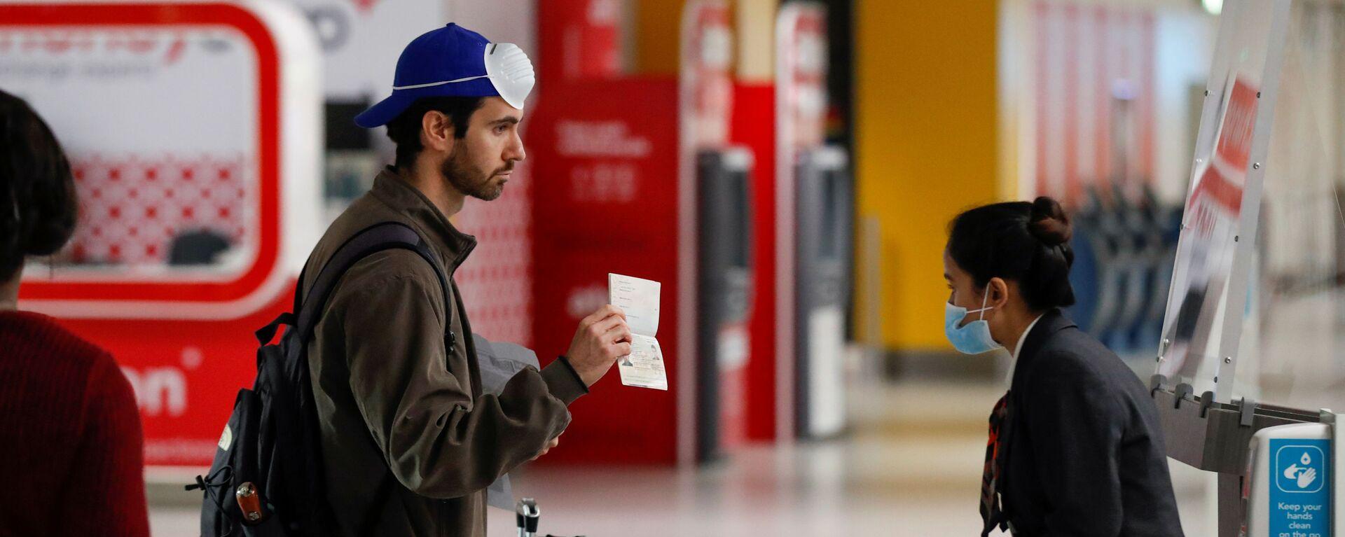 Пассажир предъявляет свой паспорт сотруднику в аэропорту Гатвик, Великобритания - Sputnik Таджикистан, 1920, 31.03.2021
