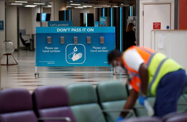 Сотрудник по уборке в маске и перчатках дезинфицирует сиденья в аэропорту Гатвик, Великобритания - Sputnik Таджикистан