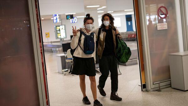 Пассажиры рейса из Амстердама в защитных масках прибывают в международный аэропорт в Афинах, Греция - Sputnik Таджикистан