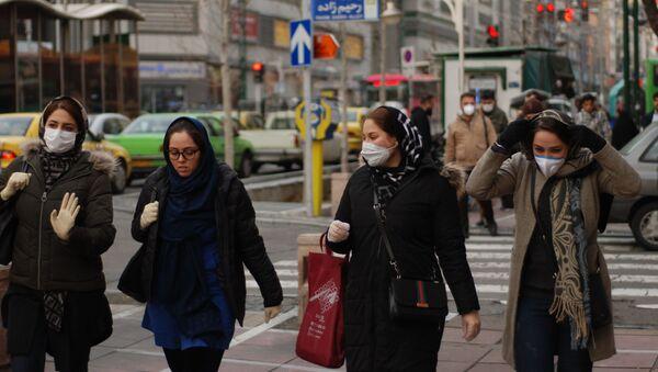 Жители Тегерана идут по одной из центральных улиц в медицинских масках - Sputnik Тоҷикистон