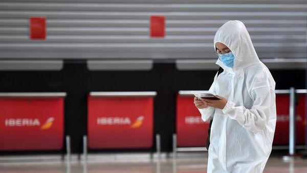 Пассажир, одетый в защитный костюм, ждет после регистрации на рейс в Пекине - Sputnik Тоҷикистон