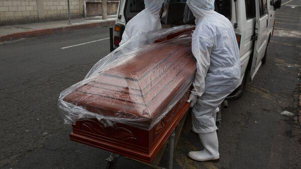 Работники похоронного бюро выносят гроб из машины - Sputnik Тоҷикистон