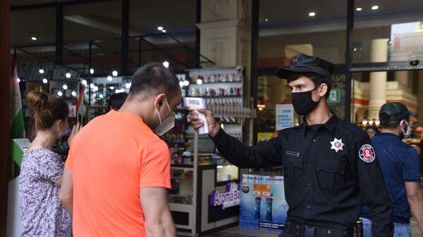 Сотрудник охраны рынка Мехргон проверяет температуру у посетителя - Sputnik Таджикистан