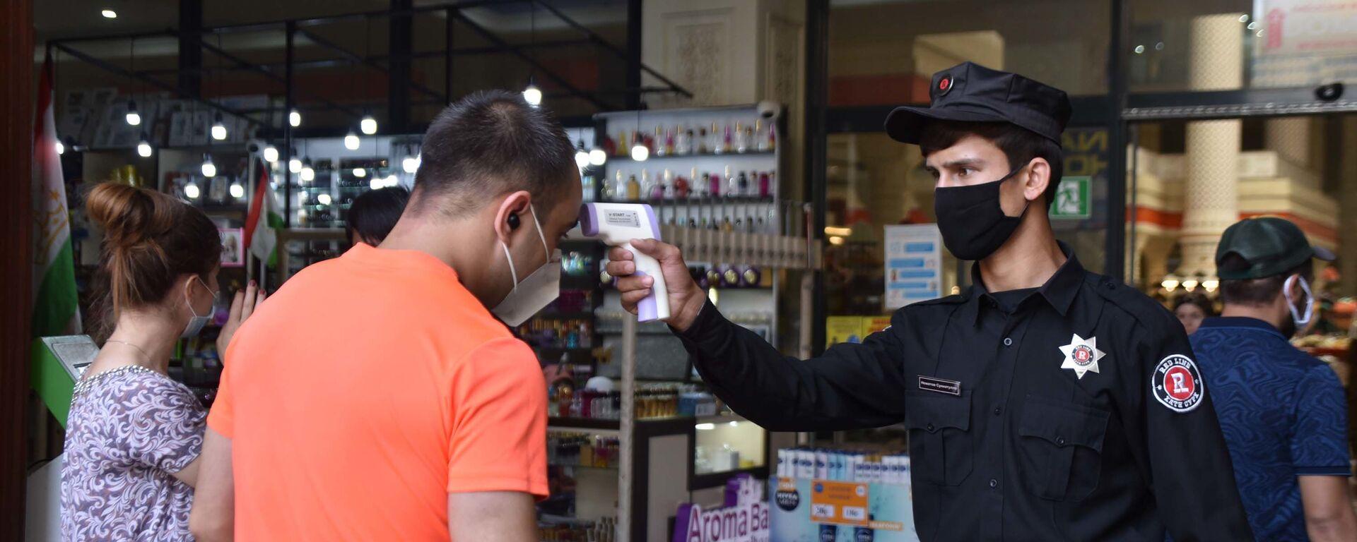 Сотрудник охраны рынка Мехргон проверяет температуру у посетителя - Sputnik Таджикистан, 1920, 13.02.2021