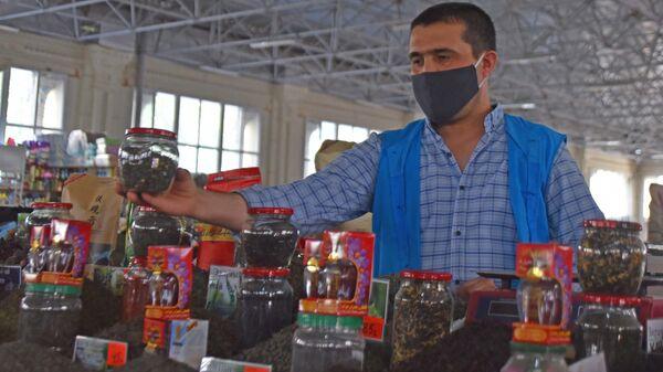 Продавец расставляет товары на рынке Мехргон - Sputnik Таджикистан