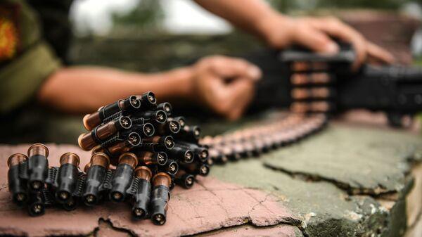 Военнослужащий мотострелкового полка Таманской дивизии снаряжает холостыми патронами  во время учений пулемет в Подмосковье - Sputnik Таджикистан